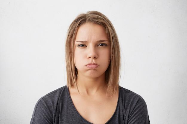 Jovem mulher bonita com penteado da moda de olhos escuros, suéter cinza casual soprando os lábios, sendo insatisfeito isolado.
