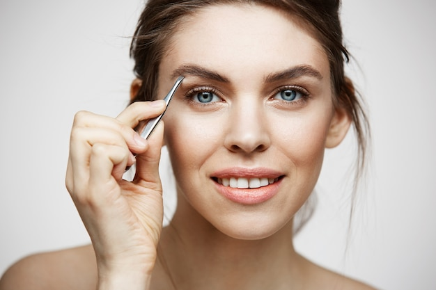 Jovem mulher bonita com perfeita pele limpa tweeze sobrancelhas. tratamento facial.