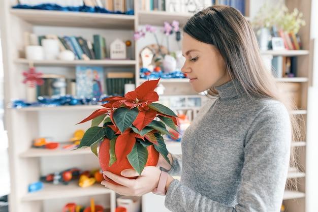 Jovem mulher bonita com poinsétia de flor vermelha de natal