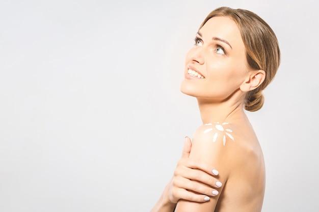 Jovem mulher bonita com protetor solar em forma de sol. linda mulher pronta para o tratamento bronzeador. sol de loção de proteção solar desenhando no ombro da mulher. isolado no fundo branco.