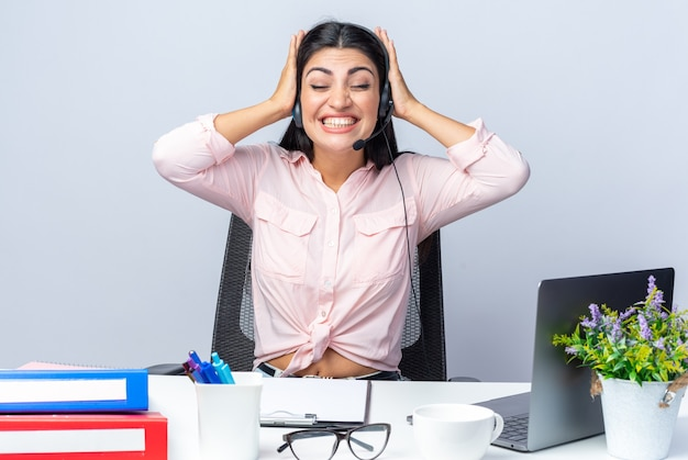 Jovem mulher bonita com roupas casuais com fones de ouvido e microfone feliz e animada de mãos dadas na cabeça dela, sentada à mesa com o laptop em branco