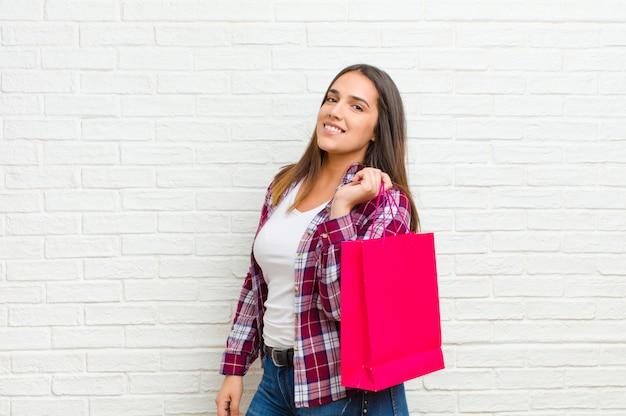 Jovem mulher bonita com sacos de compras contra a textura da parede de tijolo