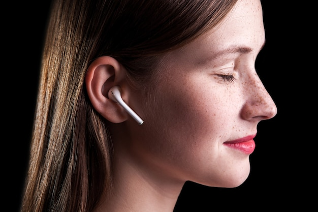 Jovem mulher bonita com sardas e fones de ouvido sem fio nas orelhas. estúdio filmado em fundo preto.