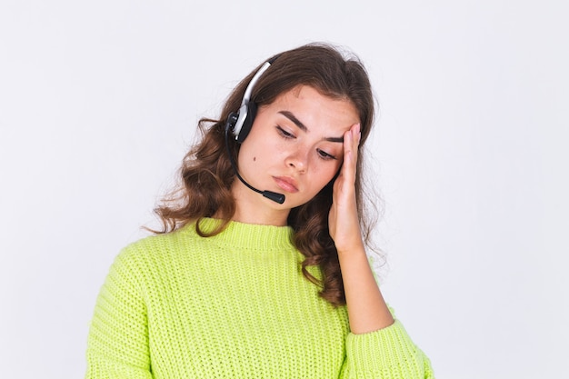 Jovem mulher bonita com sardas maquiagem leve em um suéter na parede branca com fones de ouvido trabalhador da linha de apoio gerente de call center triste cansado entediado