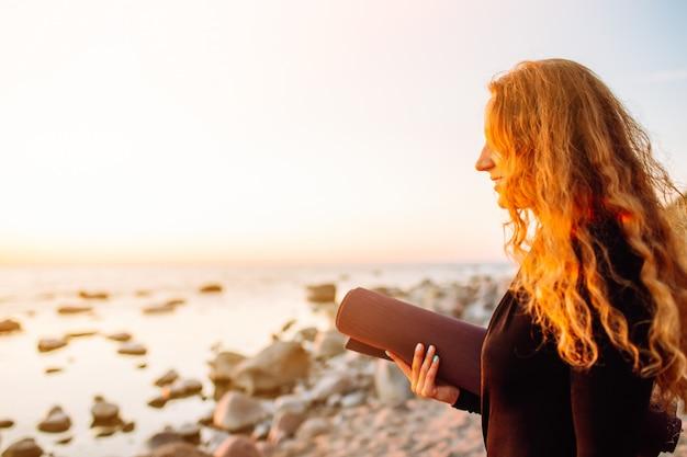 Jovem mulher bonita com tapete de ioga em pé na praia no verão ao pôr do sol e pronto para treino.