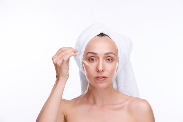 Jovem mulher bonita com toalha branca na cabeça vai aplicar soro rejuvenescedor no rosto em pé