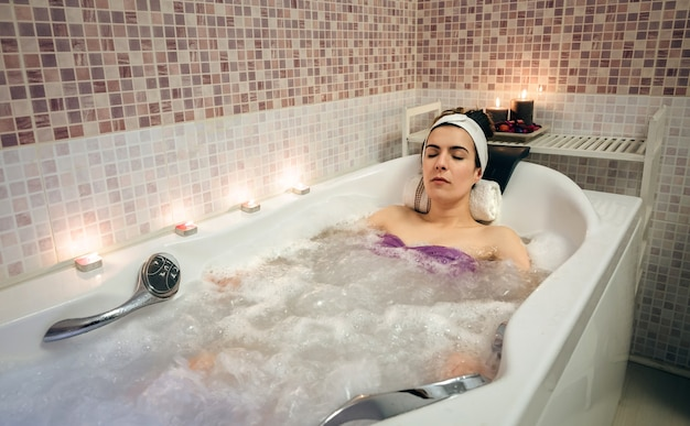 Jovem mulher bonita com turbante deitado na banheira, fazendo tratamento de hidroterapia. conceito de saúde e beleza.