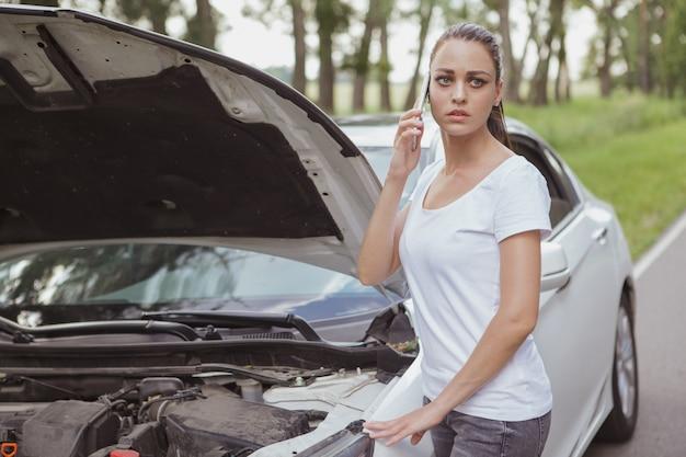 Jovem mulher bonita com um carro quebrado na estrada