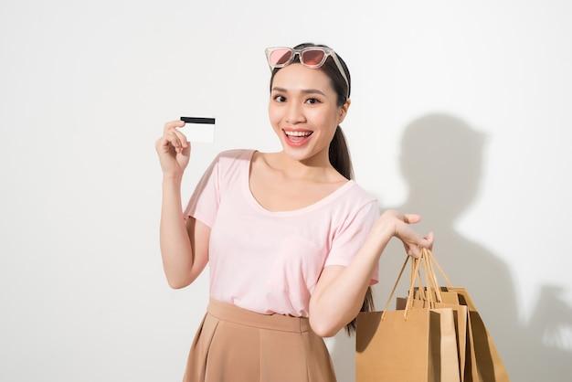 Jovem mulher bonita com um cartão de crédito na mão e segurando sacolas de compras