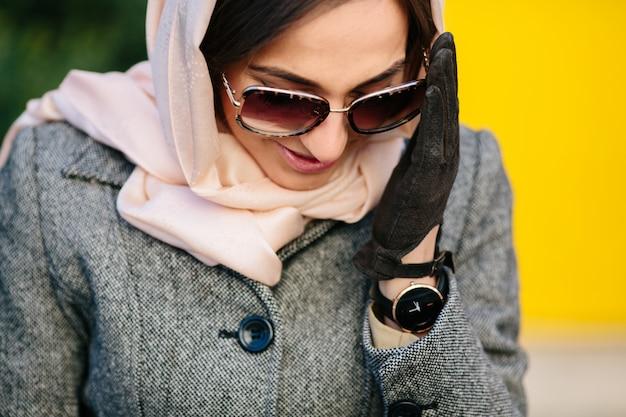 Jovem mulher bonita com um casaco sentada num banco do parque