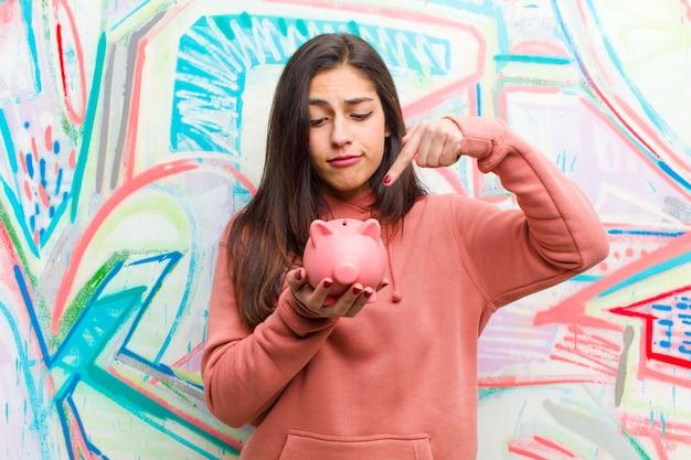 Jovem mulher bonita com um cofrinho contra parede grafite