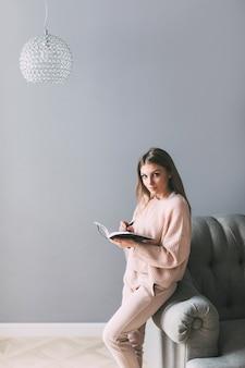 Jovem mulher bonita com um livro perto da cadeira em casa. escrevendo no diário.