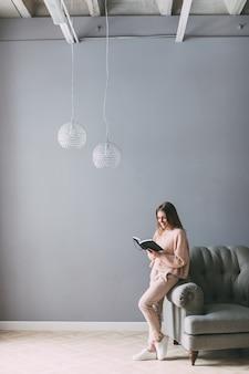 Jovem mulher bonita com um livro perto da cadeira em casa.