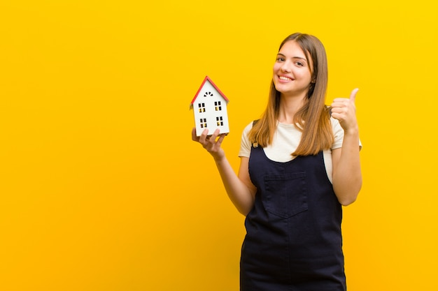 Jovem mulher bonita com um modelo de casa contra fundo laranja