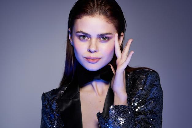 Jovem mulher bonita com um olhar sexy em uma jaqueta brilhante