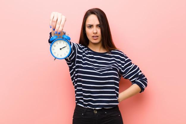 Jovem mulher bonita com um relógio. conceito de tempo