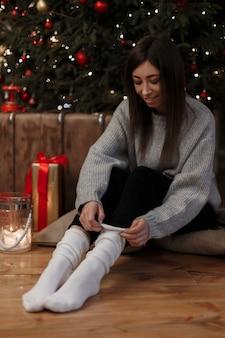 Jovem mulher bonita com um suéter vintage de malha em jeans preto se senta no chão perto da árvore de natal em um quarto aconchegante e usa meias brancas quentes. garota linda