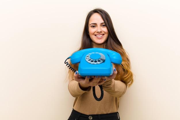 Jovem mulher bonita com um telefone azul vintage