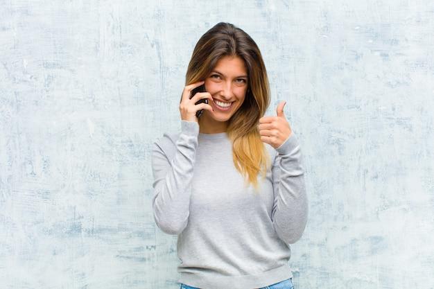 Jovem mulher bonita com um telefone inteligente contra parede grunge