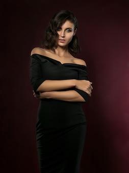 Jovem mulher bonita com um vestido de noite preto posando sobre fundo vermelho escuro.