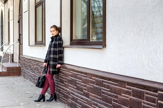 Jovem mulher bonita com uma bolsa elegante está de pé na rua