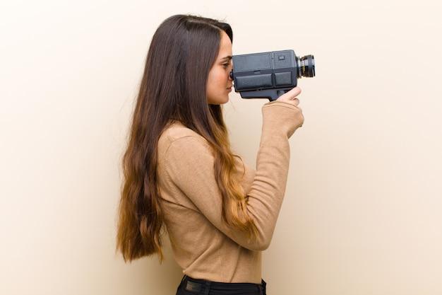 Jovem mulher bonita com uma câmera de vídeo vintage