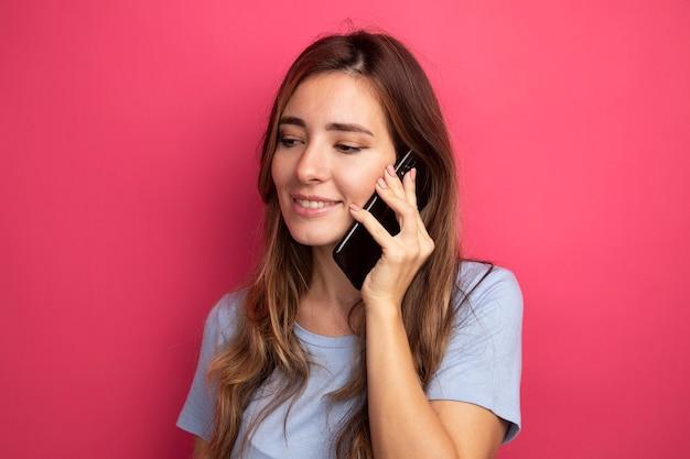Jovem mulher bonita com uma camiseta azul falando no celular e sorrindo alegremente em pé sobre o rosa