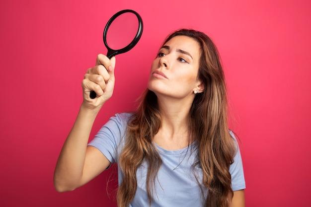 Jovem mulher bonita com uma camiseta azul segurando uma lupa e olhando para ela intrigada em pé sobre rosa