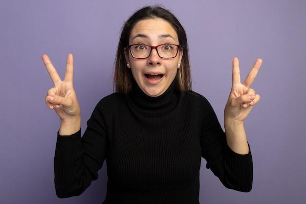 Jovem mulher bonita com uma gola alta preta e óculos olhando para a frente feliz e animada mostrando o sinal v com as duas mãos em pé sobre a parede roxa