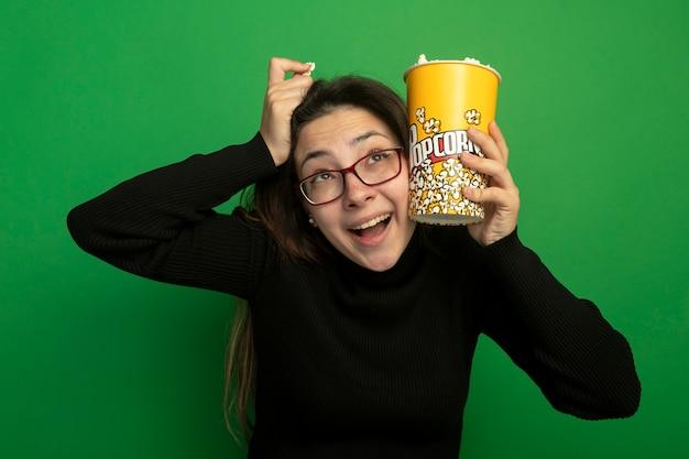 Jovem mulher bonita com uma gola alta preta e óculos segurando um balde com pipoca, olhando para cima feliz e animada em pé sobre a parede verde