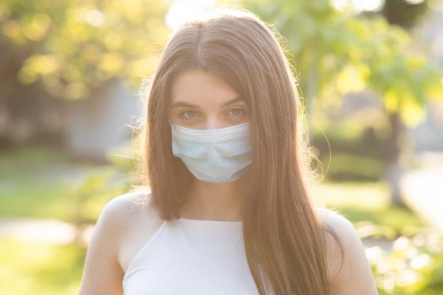Jovem mulher bonita com uma máscara facial no parque