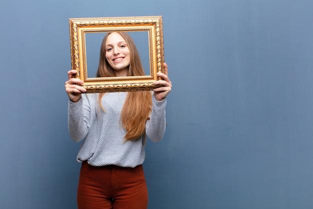 Jovem mulher bonita com uma moldura barroca contra parede azul com um espaço de cópia