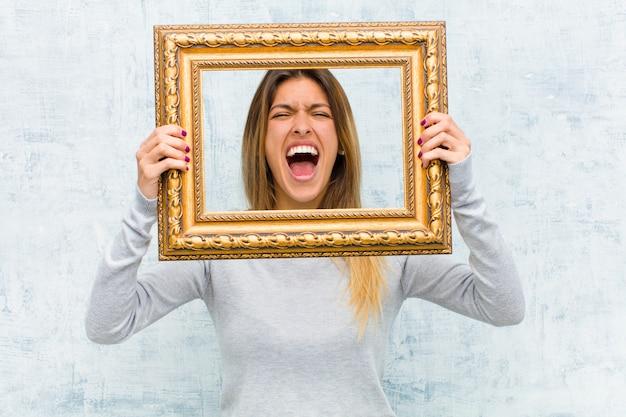 Jovem mulher bonita com uma moldura barroca contra parede grunge