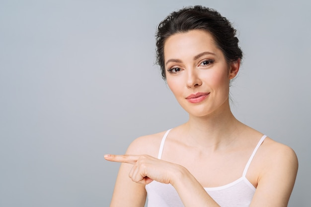 Jovem mulher bonita com uma pele perfeita gesticulando para copiar o conceito de beleza e spa de cosmetologia espacial