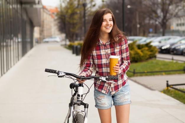 Jovem mulher bonita com uma xícara de café e uma bicicleta