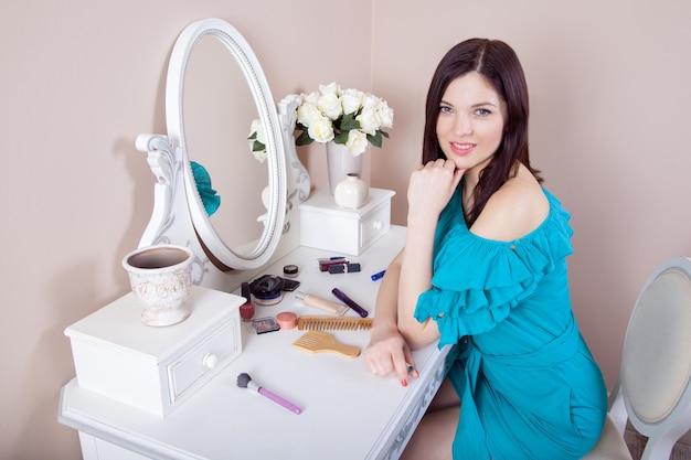 Jovem mulher bonita com vestido a aplicar maquilhagem