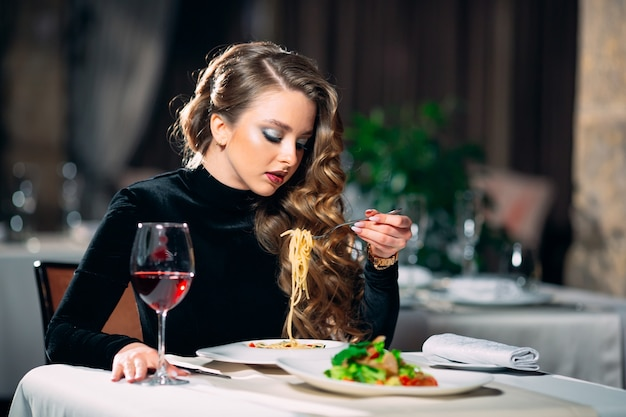 Jovem mulher bonita comendo macarrão em um restaurante.