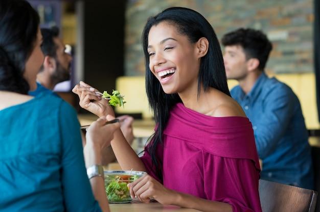 Jovem mulher bonita comendo salada