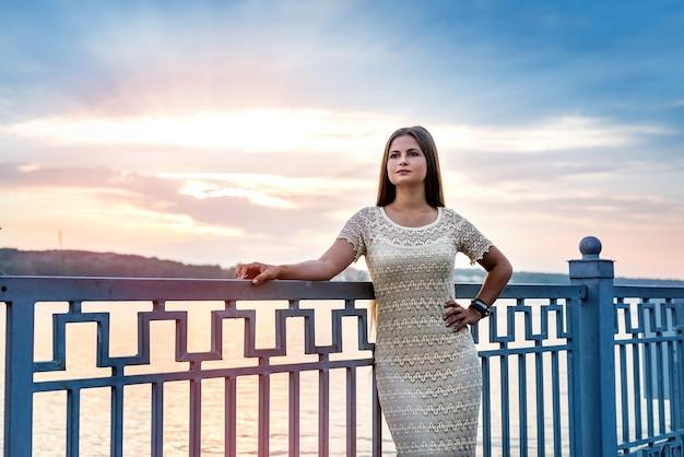 Jovem mulher bonita contra o pôr do sol no lago