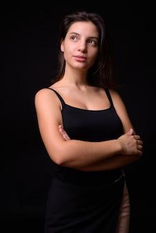 Jovem mulher bonita contra parede preta Foto Premium