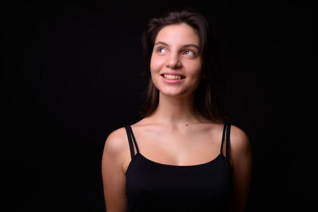 Jovem mulher bonita contra parede preta