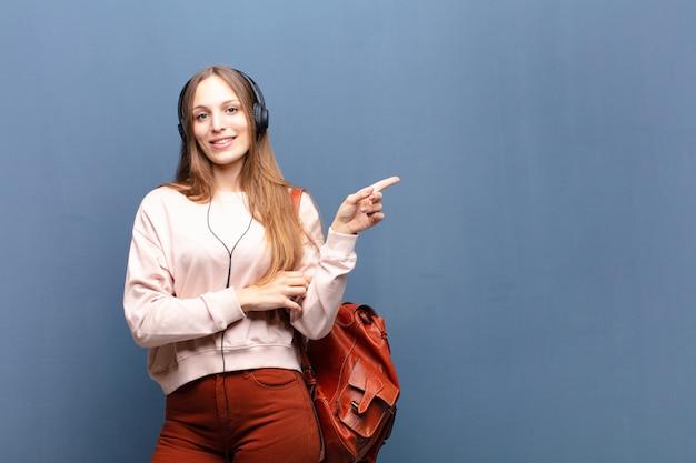 Jovem mulher bonita contra uma parede azul com um copyspace