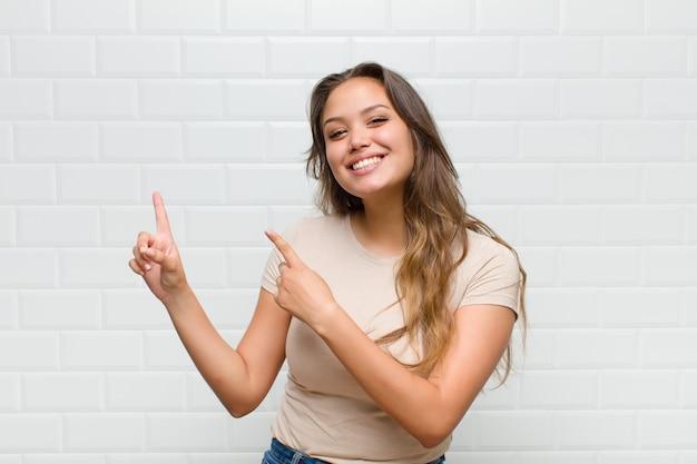 Jovem mulher bonita contra uma parede branca