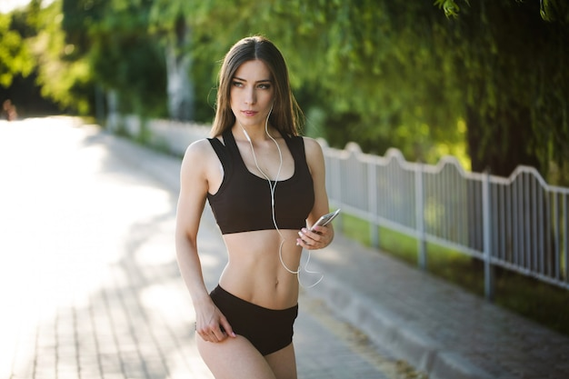 Jovem mulher bonita correndo no parque e ouvir música com fones de ouvido