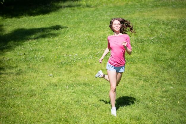 Jovem mulher bonita correndo no parque