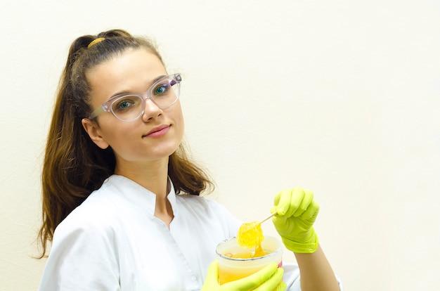 Jovem mulher bonita, cosmetologista garota, mestre de depilação em luvas verdes está conduzindo um procedimento de shugaring. pasta de açúcar nas mãos femininas.