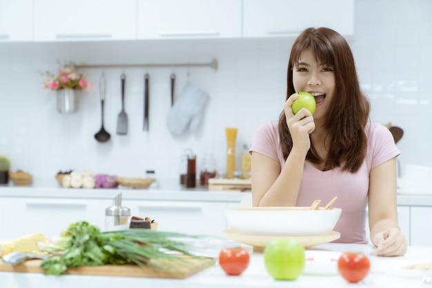 Jovem mulher bonita cuida de sua saúde comendo salada e frutas em vez de comer gordura e calorias