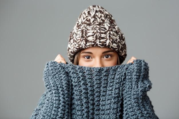 Jovem mulher bonita de cabelos louro vestindo chapéu knited e camisola, escondendo o rosto na gola em cinza. copie o espaço.