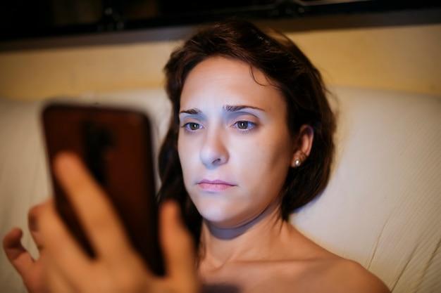 Jovem mulher bonita de meia-idade à noite com conceito de dependência de telefone celular