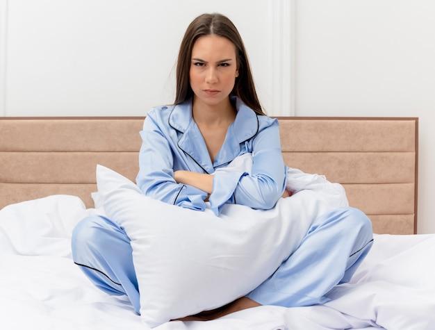 Jovem mulher bonita de pijama azul sentada na cama com travesseiro e rosto sério ficando descontente no interior do quarto